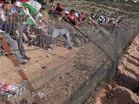 Bil'in villagers tear down the illegal fence.