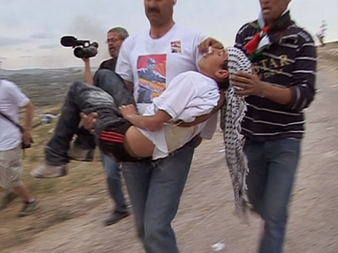 A wounded villager is carried from the field.