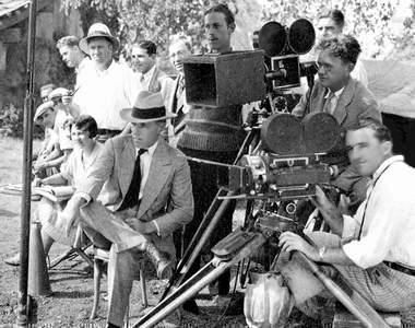 "D. W. Griffith (with hat) under camera. Struss behind the lens, same camera ""Drums of Love,"" 1928."