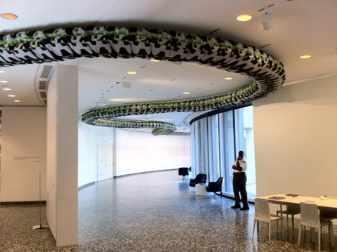 """Snake Ceiling,"" an installation of children's backpacks."