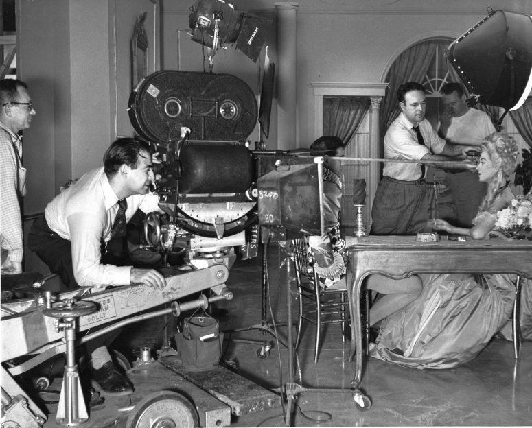 Shooting a commercial for his New York-based firm MPO Videotronics in the early 1960s, Hirschfeld checks his frame. Behind him is operator Sol Roizman. Pulling tape is Tony Brooke.