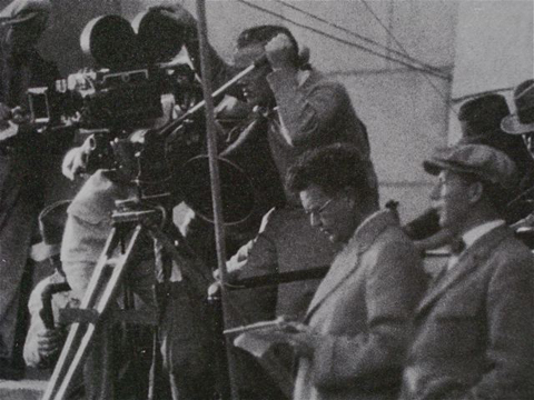 Struss making notes for multiple exposure setup on church steps, Murnau at his left in cap (detail).