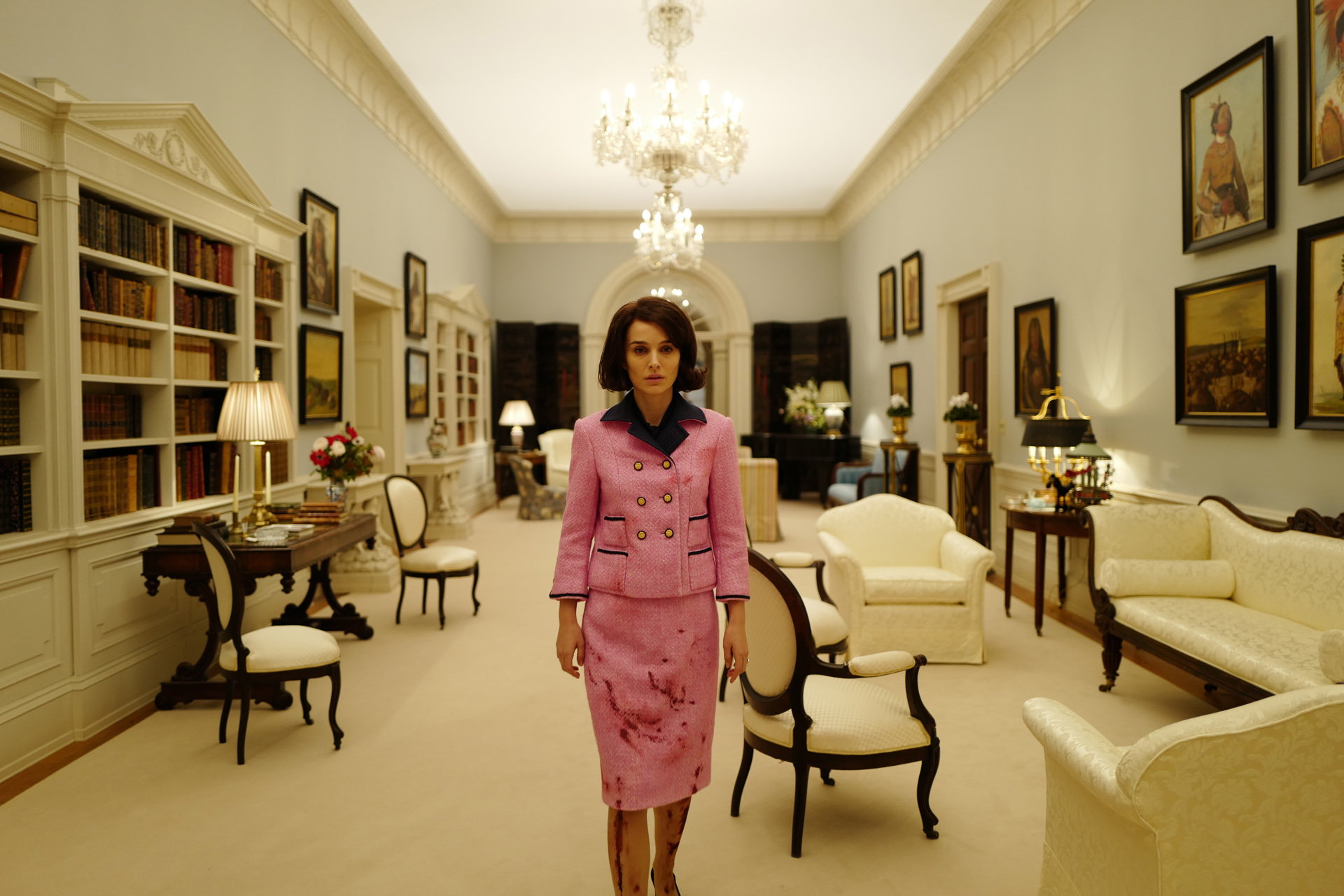 Natalie Portman stands in a White House set with a luminous ceiling