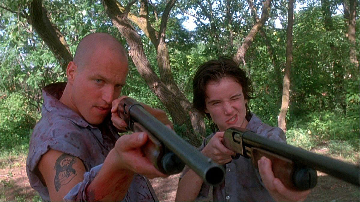 Mickey (Woody Harrelson) and Mallory (Juliette Lewis) aim shotguns squarely into the face of the media in Natural Born Killers (1995).