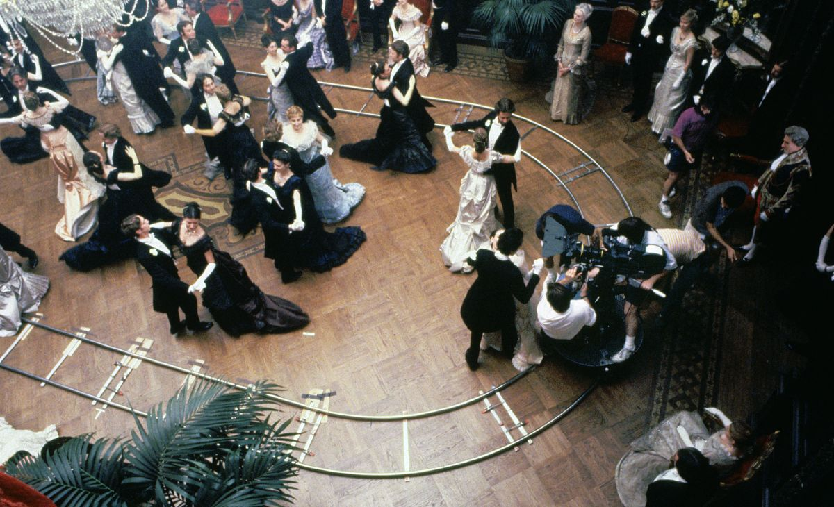 The camera crew dollies around costumed dancers during an elaborate ballroom sequence while filming the elegant, lavishly detailed drama The Age of Innocence