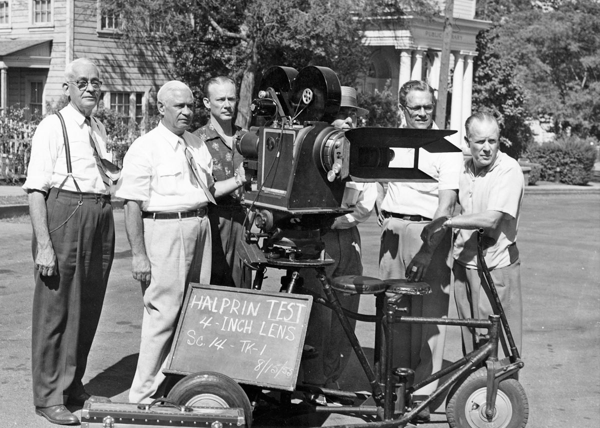 Following decades of work behind the camera, Sol Halprin, ASC (seen second from left ) became 20th Century Fox's executive director of photography. Him, studio engineer Grover Laube (far left ) and chief research engineer Earl Sponable (not in this photo), developed the widescreen CinemaScope 55 system being tested on this summer day in 1955. The camera is a Fox 4x55, a Mitchell 70mm camera built in the 1930s and converted by the Fox camera department to handle a 55.625mm wide, 8-perf-high negative. Bausch & Lomb made custom anamorphic lenses for the unique format. Unfortunately, tests with CinemaScope 55 — used to shoot the lavish musicals The King and I and Carousel (both released in 1956) — convinced the studio that the audience did not perceive the promised quality difference, meaning the added expense in production and post was not worthwhile. As a result, Fox abandoned CinemaScope 55 in favor of the more-established 65mm Todd-AO system.