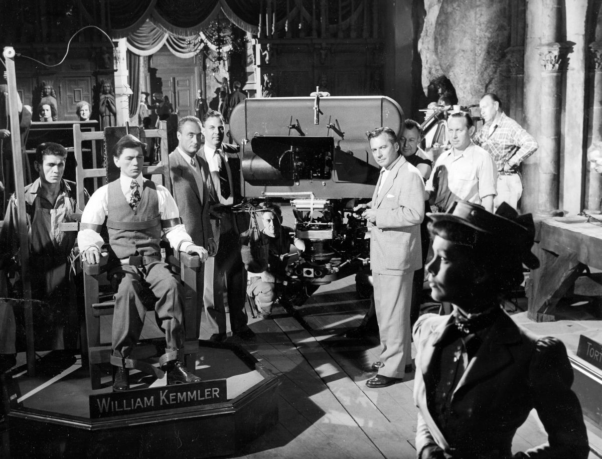 Actors Charles Bronson (far left) and Phyllis Kirk (foreground) are positioned for a take during the production of House of Wax (1953), one of the most popular of the stereoscopic films made during the 3D craze of the 1950s. Warner Bros. unit photographer Jack Woods snapped this shot as the Natural Vision camera unit — designed by Milton Gunzberg — was about to roll. House of Wax was screened using dual interlocked 35mm projection with polarized glasses. The film was re-released in the late 1970s in both single-strip 35mm Stereovision 3D and Stereovision's pioneering 70mm 3D process. Ironically, House of Wax director André De Toth (left of camera, in white vest, next to studio exec Jack M. Warner) was blind in one eye and unable to actually see his film's 3D effects. To that end, he relied on ASCcinematographers Bert Glennon, Peverell Marley and Robert Burks (right, in front of the camera), operator Howard Schwartz (far right, in white shirt), and 3D consultant Lothrop B. Worth (crouching under camera), both of whom later became Society members.