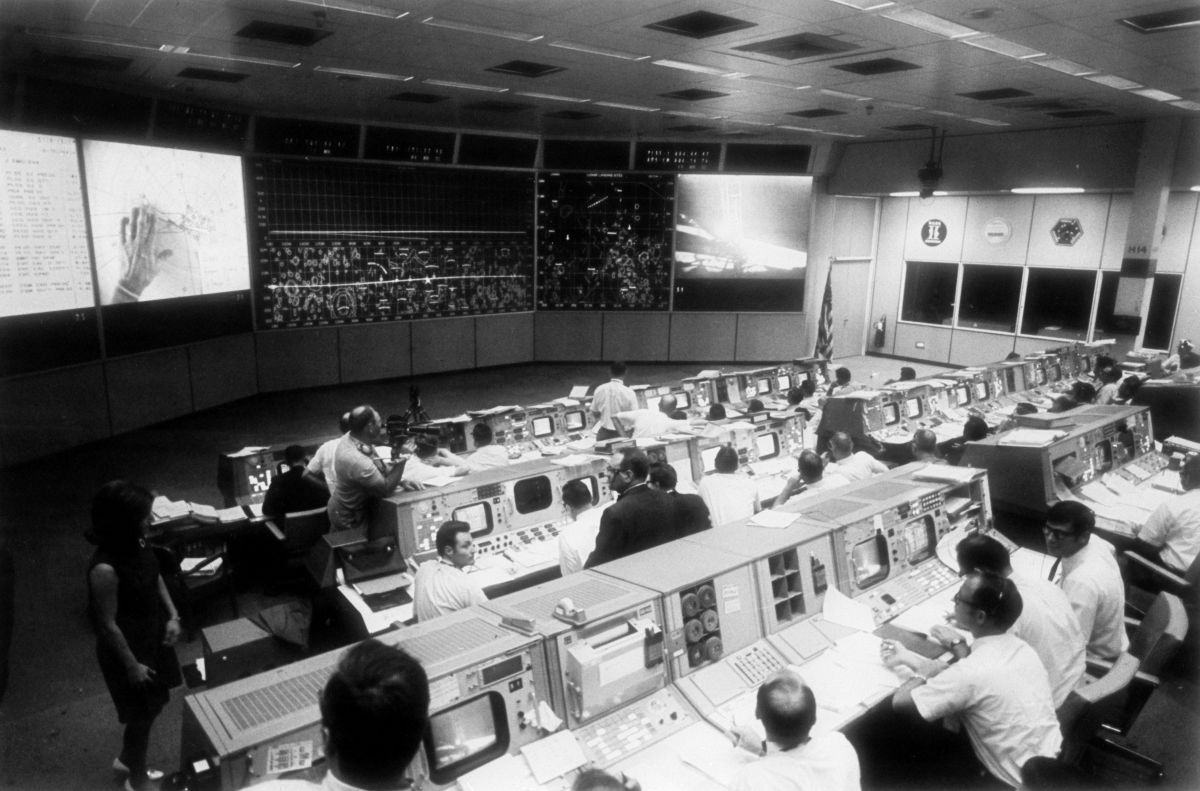 The scene inside the windowless, dimly lit Mission Operations Control Room at NASA's Manned Spacecraft Center during the Apollo 11 flight. Lead Cameraman Bob Bird of Houston's A-V Corporation  (standing, at left) moves about filming with his Beaulieu R16B camera, equipped with 9.5-95mm zoom lens. Overhead can be seen banks of mixed blue fluorescent and incandescent lamps with color temperature close to daylight and a light level ranging from 7 to 16 footcandles.