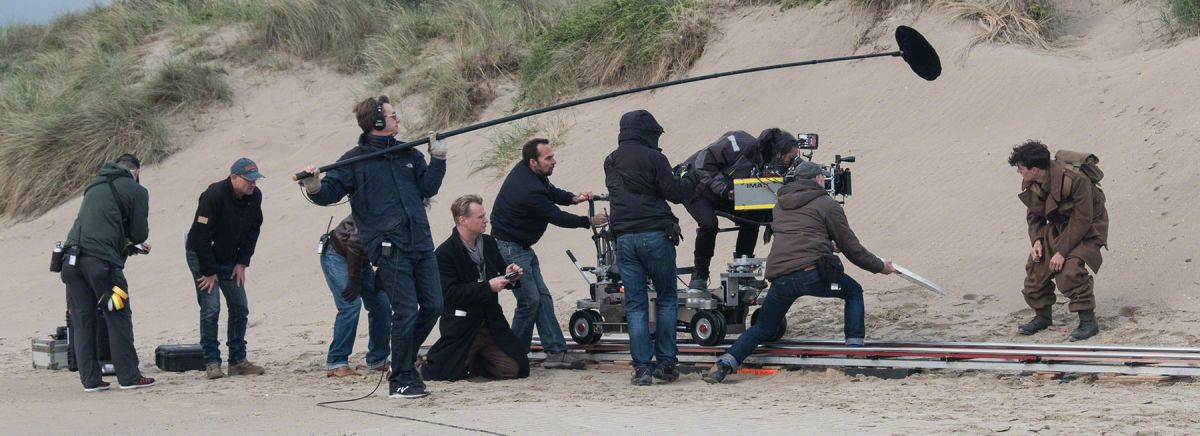 The Dunkirk production crew sets their next shot on the beach.