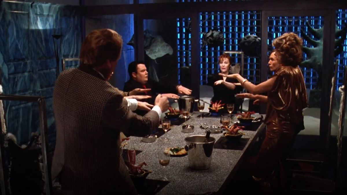 The dinner party scene showcases the dark, moody, industrial-style atmosphere of the re-modeled home and Ackerman's lighting.