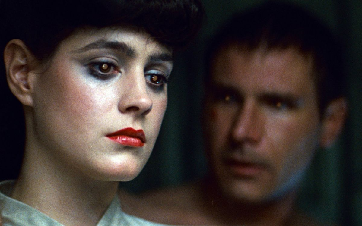 "In Blade Runner (1982), Rick Deckard (Harrison Ford) finds himself drawn to the mysterious replicant Rachael (Sean Young). One of the identifying characteristics of replicants is a strange glowing quality of the eyes. Cinematographer Jordan Cronenweth, ASC revealed his technique in American Cinematographer: ""We'd use a two-way mirror ― 50% transmission, 50% transmission, 50% reflection ― placed in front of the [camera] lens at a 45 degree angle. Then we'd project a light into the mirror so that it would be reflected into the eyes of the subject along the optical axis of the lens. Sometimes we'd use very subtle colored gels to add color to the eyes."""