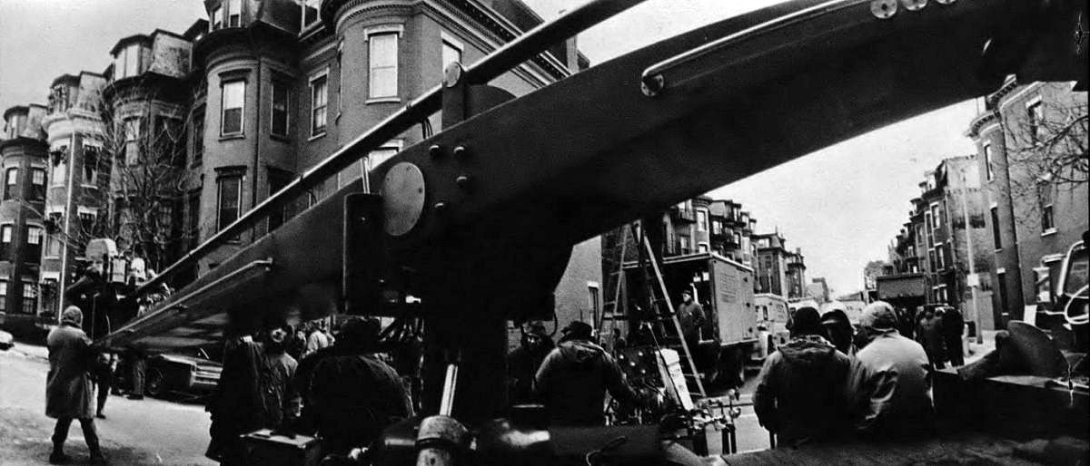 "A Chapman camera crane, with Panavision camera mounted, dominates the scene as 20th Century-Fox crew films The Boston Strangler on location. Peculiar apparent distortion of the crane is due to the extreme wide-angle ""fisheye"" lens used to take the photograph."