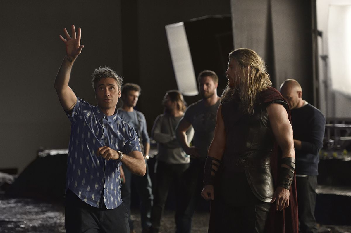 Director Taika Waititi (left) goes over a scene with Chris Hemsworth (portraying Thor).