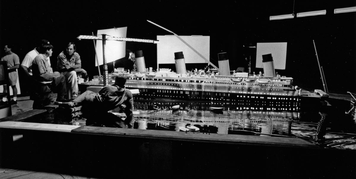 A large model of the ill-fated luxury liner HMS Titanic was set up for lighting tests during prep on the blockbuster period drama Titanic (1997), and at the center of the discussion are (from left) chief lighting technician John Buckley, Carpenter and Cameron (reclining). Of note is the Mylar sheeting around the model, simulating water, which rendered an accurate suggestion of how the huge, to-be-built ship set's complex practical lighting would play once it was positioned in the tank facility at Fox Baja Studios (seen below).