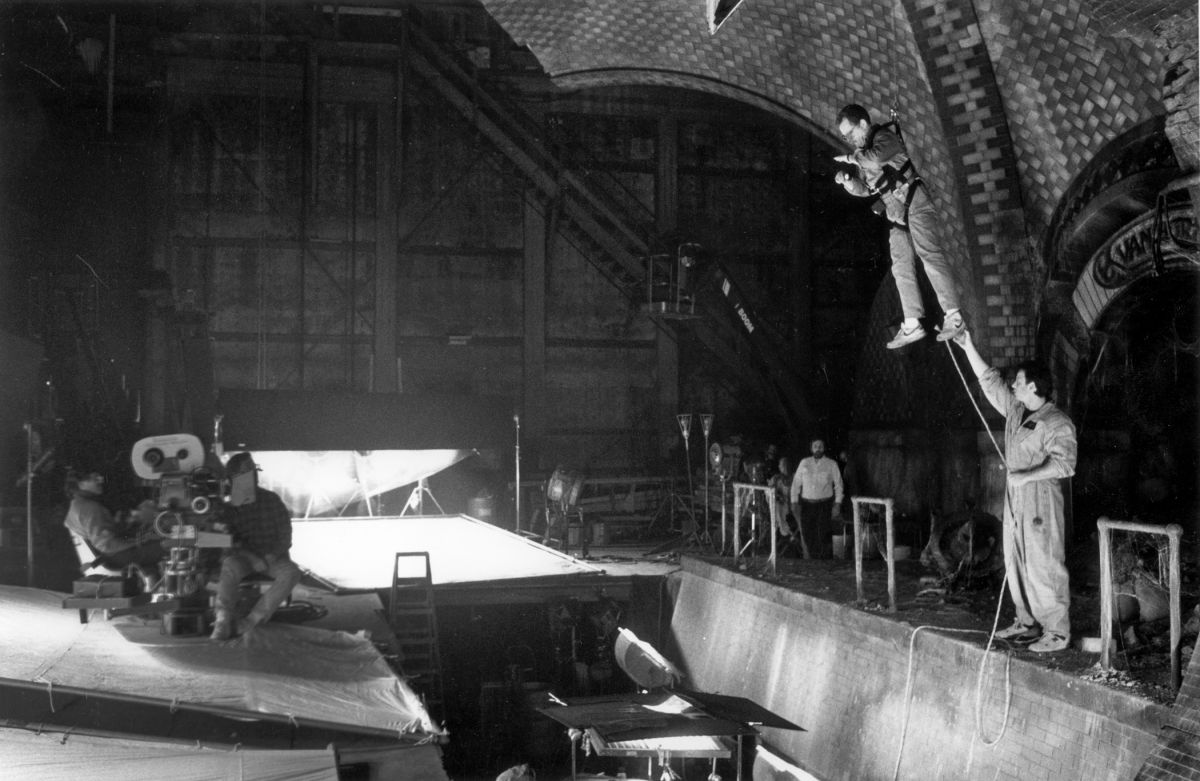 Chapman is suspended to check his light on a tricky shot while filming Ghostbusters II (1989), directed by Ivan Reitman.