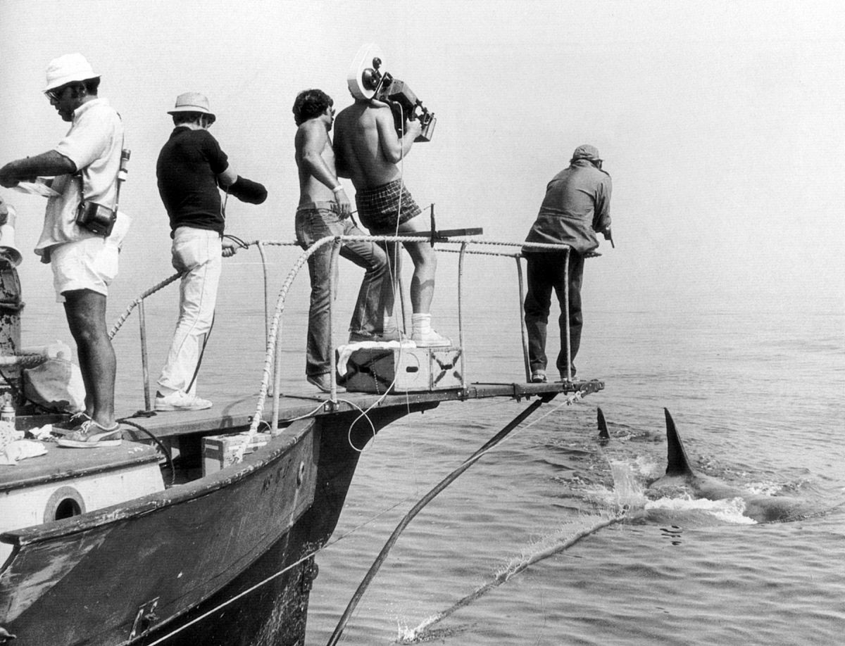 Spielberg watching from over his shoulder, Chapman hefts a Panaflex and angles in past actor Robert Shaw, capturing a memorable shot during the production of Jaws.