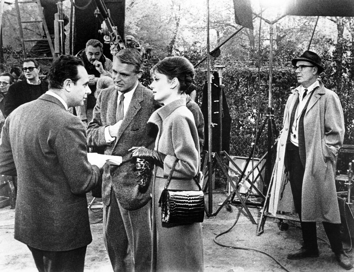 Cinematographer Charles B. Lang, Jr., ASC (far right) looks on as producer-director Stanley Donen (left) discusses upcoming action with Grant and Hepburn on a Paris location. (Photo courtesy of Everett Collection)
