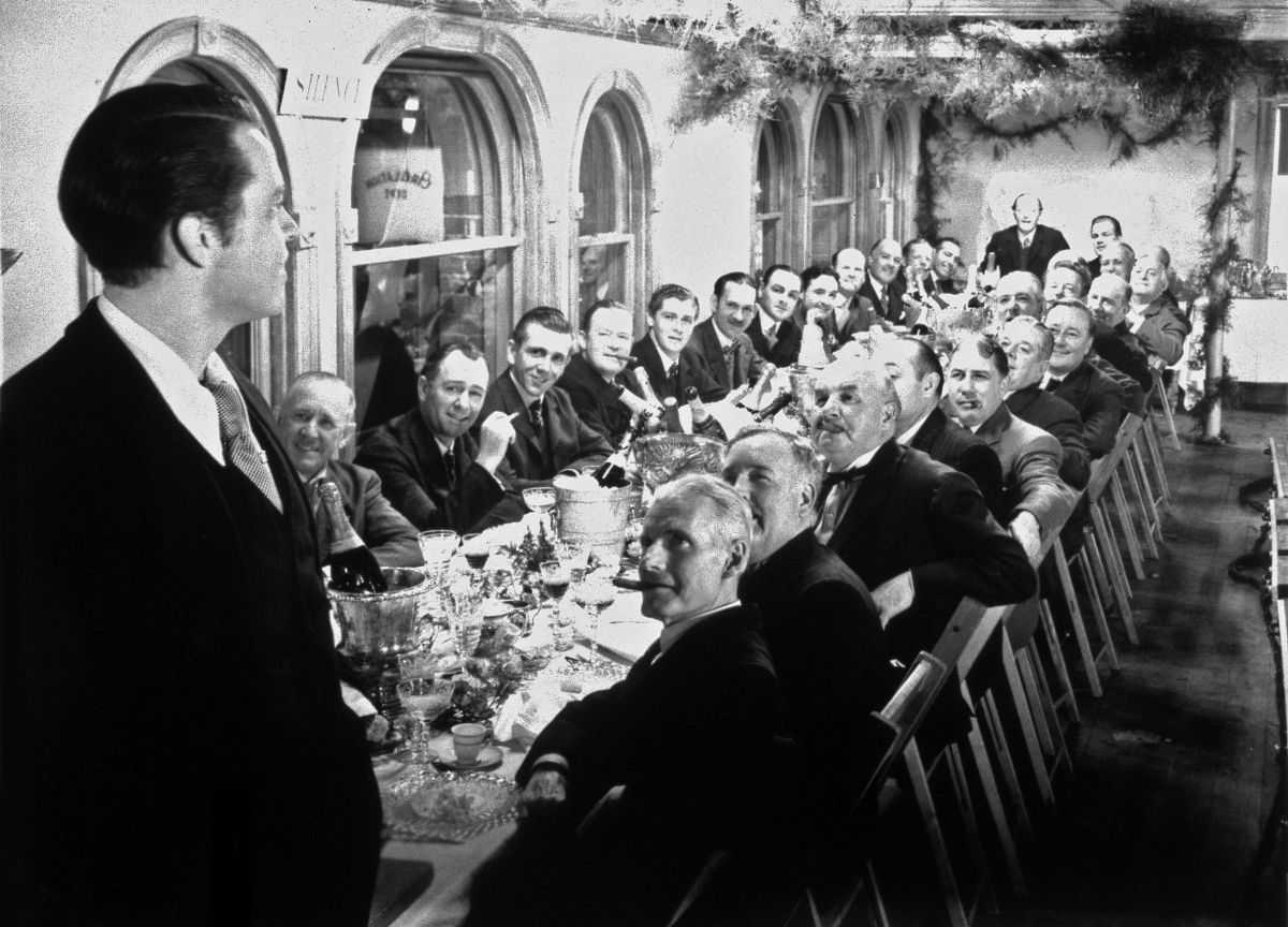 "In Citizen Kane (1941), Charles Foster Kane (Orson Welles) addresses his New York Daily Inquirer staff. This image typifies cinematographer Gregg Toland, ASC's extensive use of ""deep focus"" in the picture, rendering every element in the shot with total sharpness and allowing the audience to study the entire image. This was accomplished by Toland throughout the film with a combination of extremely high lighting levels and various pre-planned optical and visual-effects techniques."