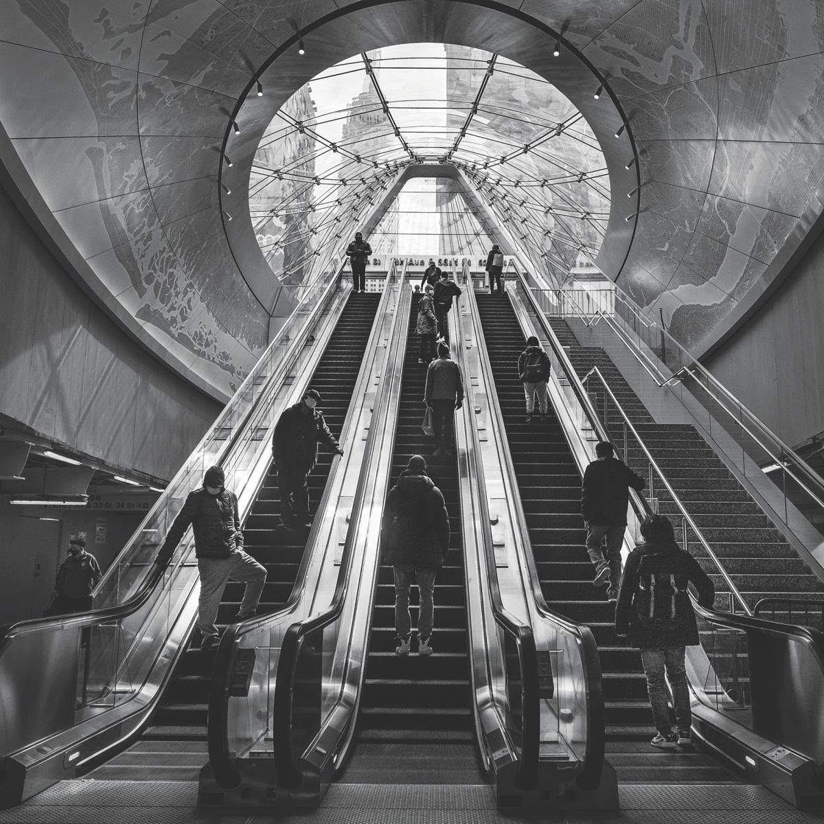 Escalator passengers at the East End Gateway of Penn Station head toward the light in the spring of 2021.