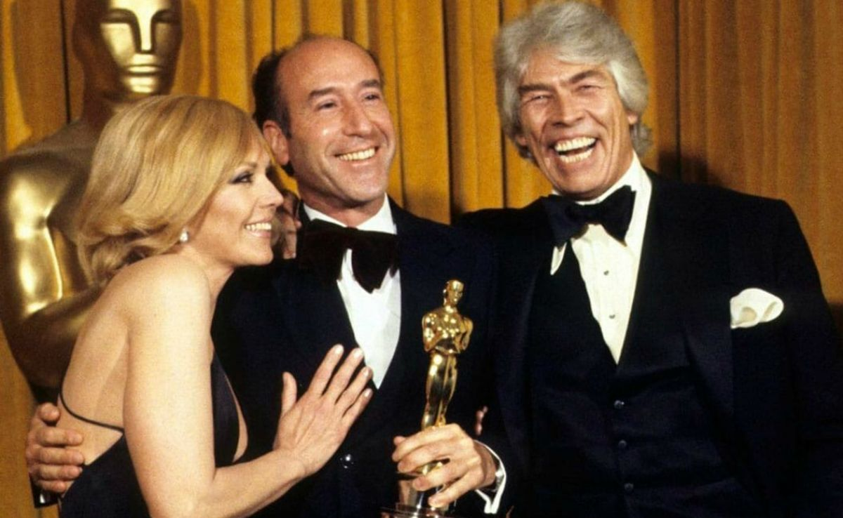 """A happy Almendros, after winning his """"Oscar,"""" accepts a congratulatory kiss from Kim Novak, while co-presenter James Coburn looks on. Almendros' unconventional lighting techniques during filming often shocked the """"Old Guard"""" American crew, but you can't argue with an Oscar."""