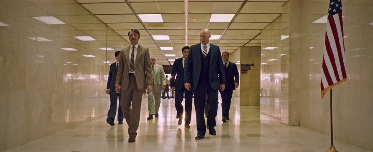 """The opening of the movie takes place at the courthouse where the case against DeLorean is about to begin,"" says Lindenlaub. ""We shot in a courthouse building in San Juan that had great hallways. We had to power the whole building with our generators after the hurricane. The opening shot starts out of focus on the 40mm anamorphic, from way down the hallway, and then the camera moves very slowly towards the entrance. We shot at 48 frames so the editor could ramp up later. We find Corey Stoll and Jason Sudeikis as they approach us; they come into focus as they come closer, and then we pull back with them. It worked really well. It gives you a feeling of the characters' stress, and it shows you that it's not clear how Hoffman is going to react in the court proceedings."""