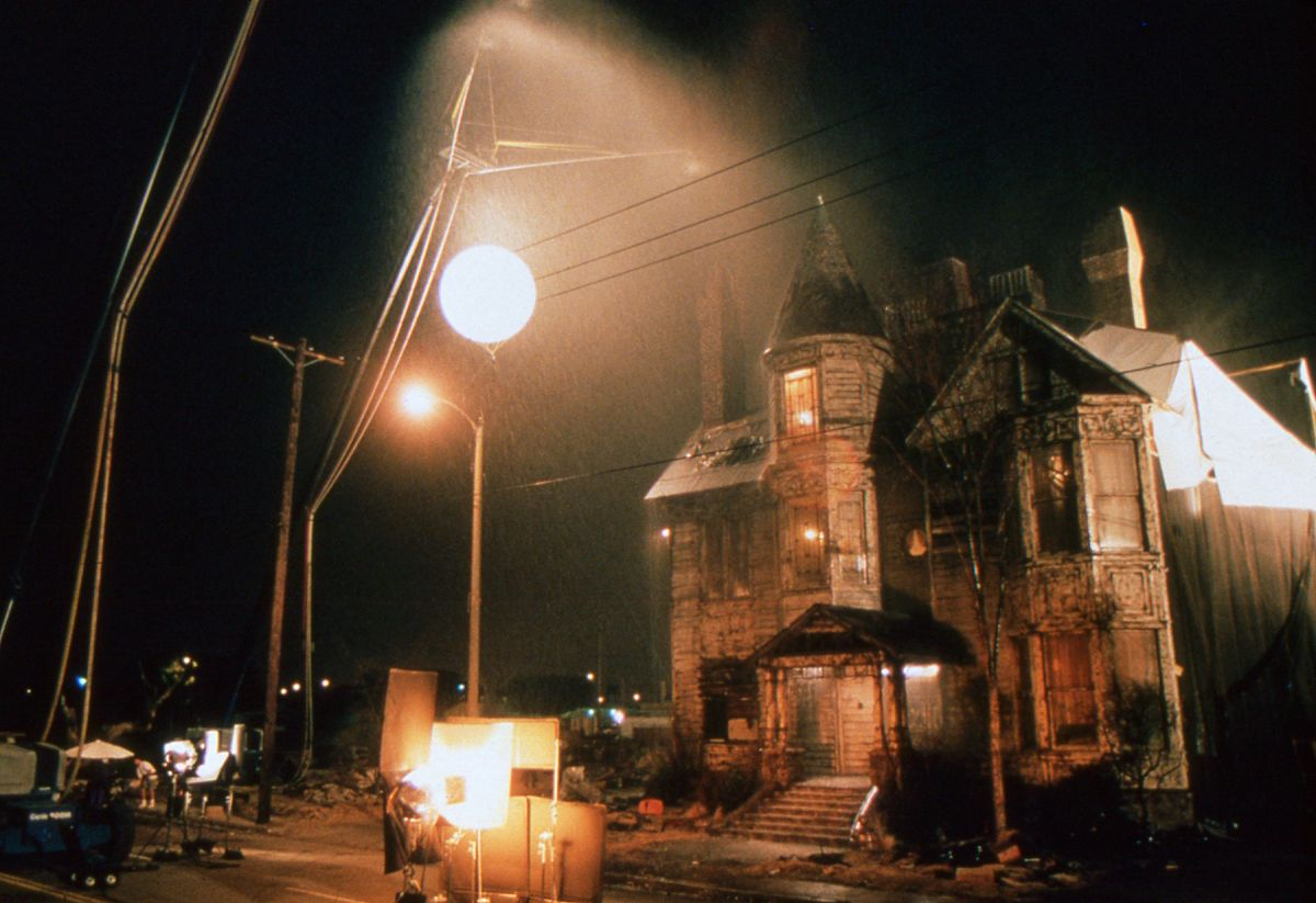 "An exterior lighting setup for the Paper Street exterior set built in San Pedro. ""We tried to stay away from the huge backlighting sources and the blue 'moonlight' look,"" sats Cronenweth. ""Most of out lights were kept pretty white. In San Pedro there are a lot of sodium-vapor lights that take on an orangey hue, so if we did occasionally use a backlight, we'd often balance it to the sodium vapors and play it as another street lamp. For the house exterior, I used an 8K tungsten balloon, which allowed us to get the light out of the way of the frame easily and get us a base exposure that was 2 or 2 1/2 stops under. We also surrounded the house with 20Ks and some of Claudio's DecaLights."""