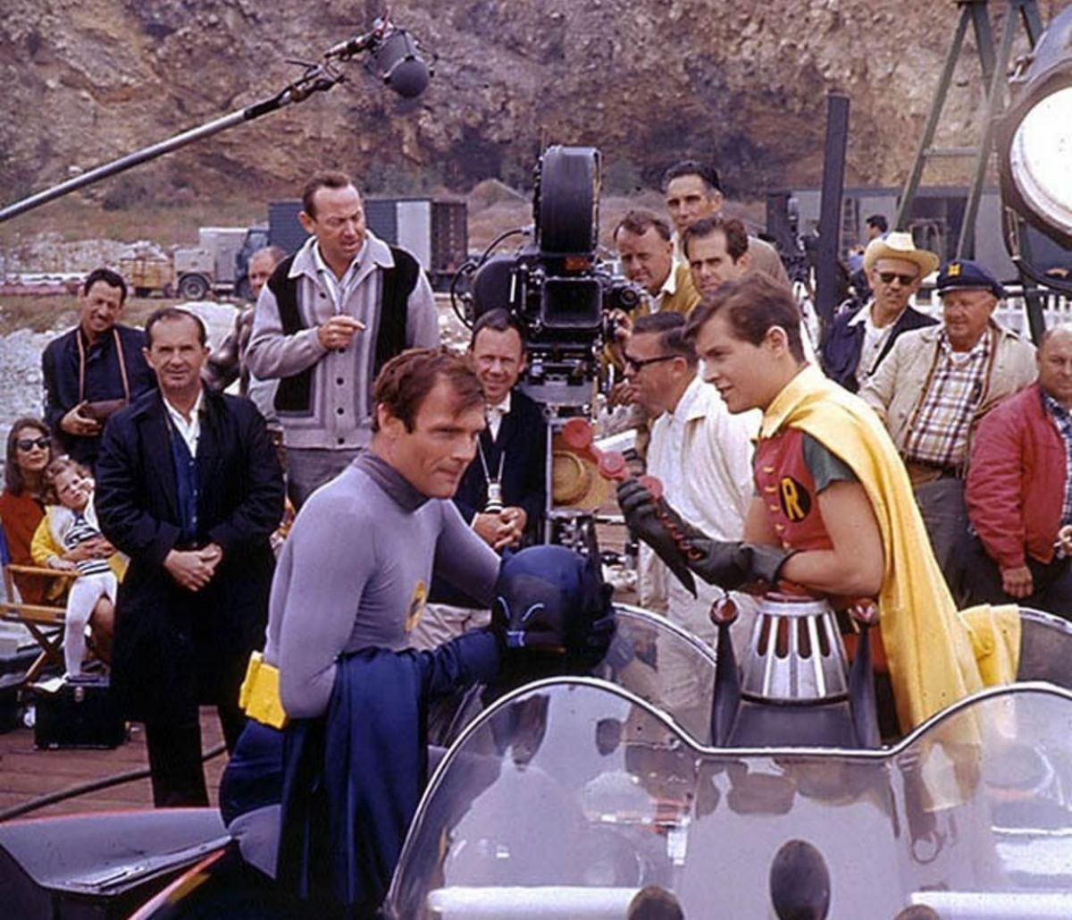 Cast and crew from 20th Century-Fox Studios on location filming a feature-length version of Batman, nation's most popular TV series. Batman (Adam West) and Robin (Burt Ward) are shown in foreground rehearsing a scene with Batmobile and Batphone, while Director Les Martinson (under camera) and Director of Photography Howard Schwartz, ASC (in striped-V sweater), check the action.