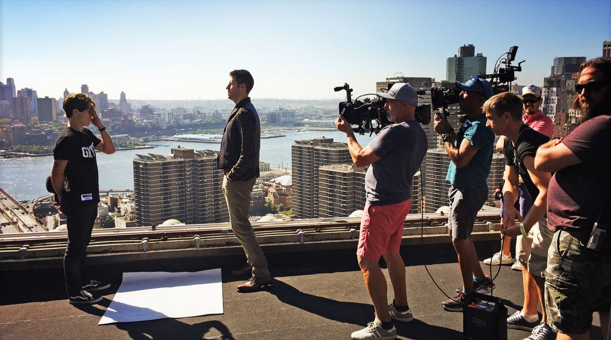 "Prepping to shoot double coverage on the rooftop of the Manhattan Municipal Building, located at the foot of the Brooklyn Bridge, Collins (in pink shorts)  blocks out angles with stand-ins. In the scene, Dr. Reinhart has tracked a backpack bomber to the rooftop, where he confronts him in the climactic scene of the episode, directed by Gus Makris. To photograph the bomber jumping off the rooftop, Collins says, ""stunts had laid out a large landing pad on the terrace two floors down and our actor started the leap, and then a stunt performer made the actual jump. We also combined some plates of the skyline and Brooklyn Bridge that our VFX company, The Molecule, composited together to alter the actual skyline on the rooftop."""