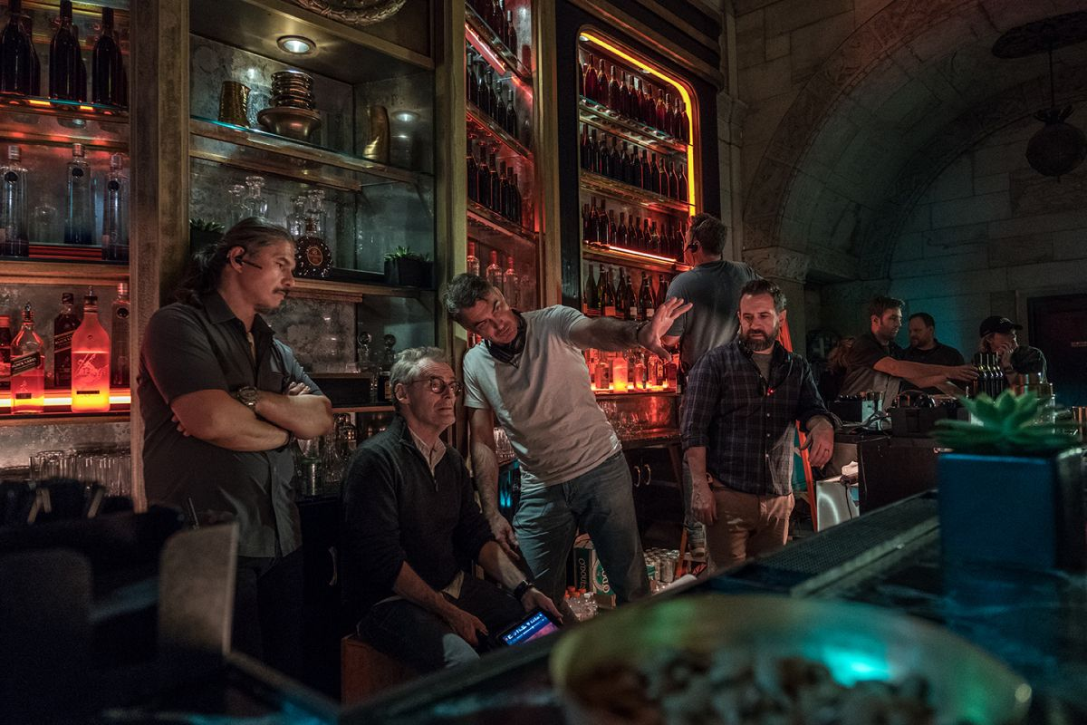 "Director Chad Stahelski (wearing white shirt) and Laustsen confer behind the bar of the Continental Hotel — actually the interior of the former Williamsburgh Savings Bank tower in Brooklyn. ""I needed someone who could light fast, because the more time I spend on lighting, the fewer takes I get,"" says the director. ""And not just someone who's going to light for me — he's got to be a world-creator. Dan was a big part of how we designed the film, even down to how we built our sets."""