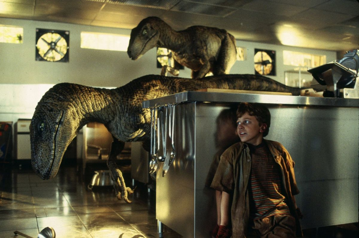 Tim (Joseph Mazzello) hides from a pair of raptors in the industrial-looking kitchen.