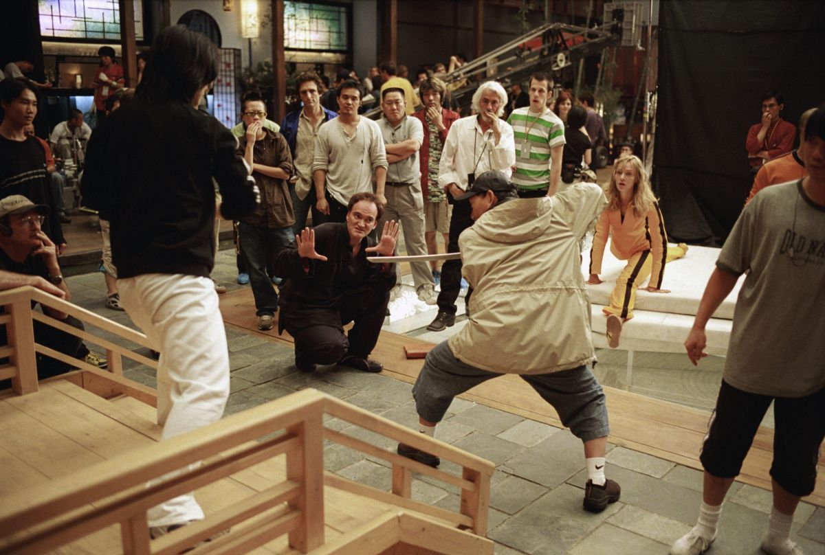 Writer-director Quentin Tarantino blocks out some swordplay with the help of the show's renowned stunt coordinator, Master Yuen-Wu Ping, as Robert Richardson, ASC (white shirt and hair) and Thurman (far right) observe with the crew.