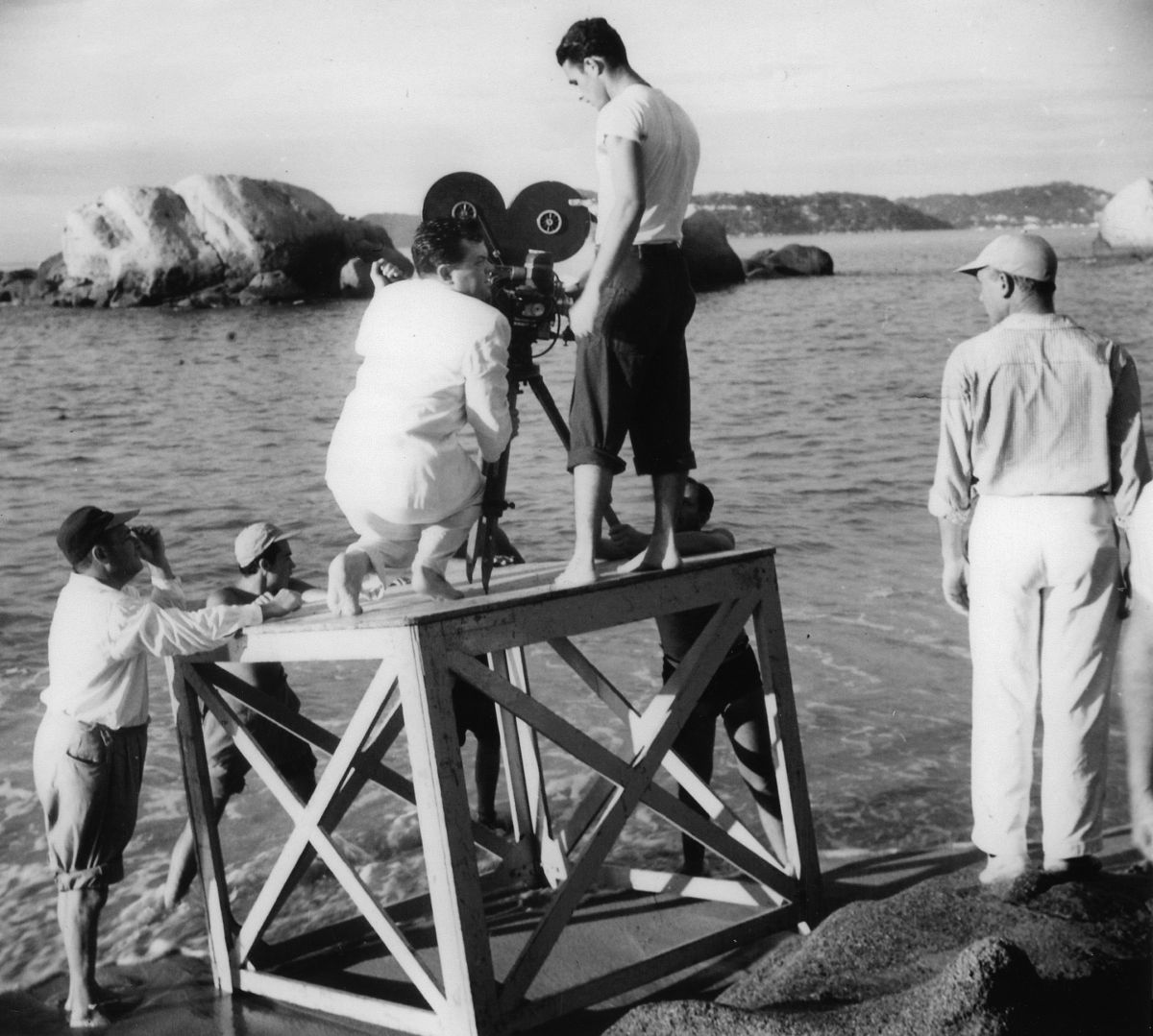 Welles examines the placement of the camera on a platform. At his side is camera assistant Richard H. Kline.