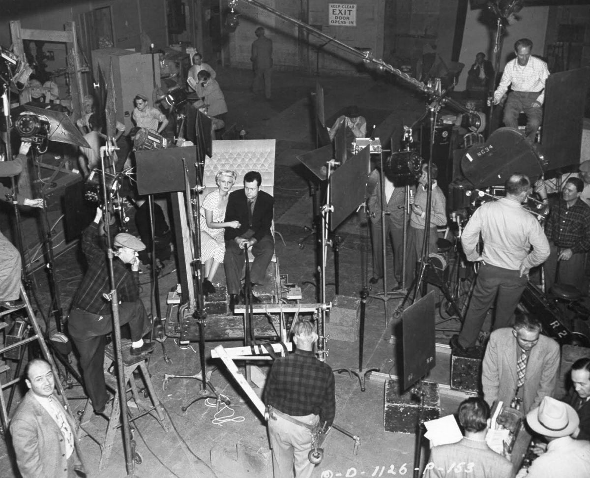Welles and Hayworth at the center of the shot while shooting on stage at Columbia Studios.