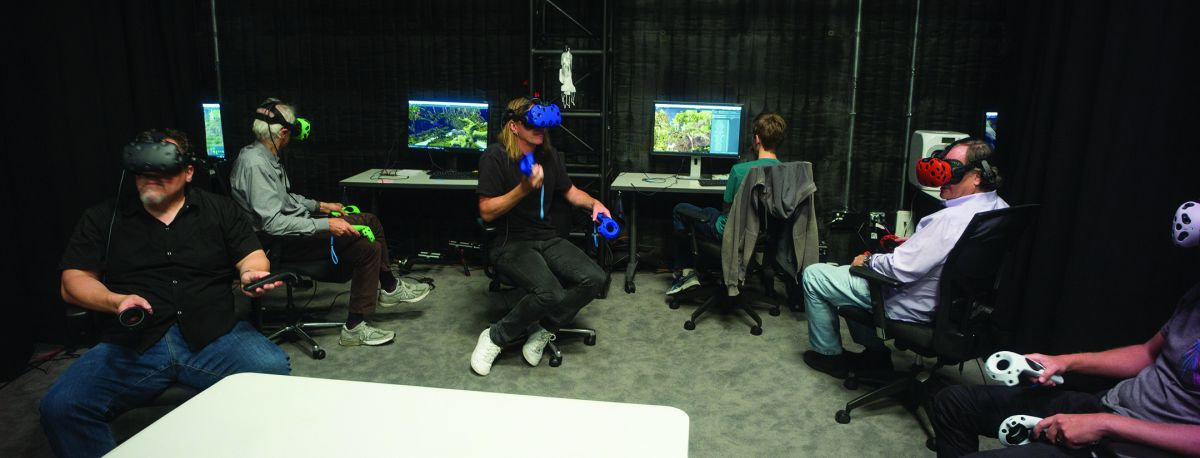 "Director Jon Favreau (far left), Deschanel (green VR rig), production designer James Chinlund (blue), Legato (red) and animation supervisor Andy Jones (white) study the previsualized world in preparation for a virtual shoot. ""At the end of the day, we. wanted this to be a Caleb Deschanel movie,"" director Jon Favreau says. ""That's why I chose him — because of all the inherent challenges that come with creating a so-called 'live-action' version of this story. There are some things in the original cartoon version that would be too intense, too graphic, too violent in live-action. But we had Caleb. He's a person who really understands framing, light and imagery. So he could bring a lot of emotion, and allude to the subject matter while still preserving the tone of a family film. The lyricism he brings to his work really serves the story well."""