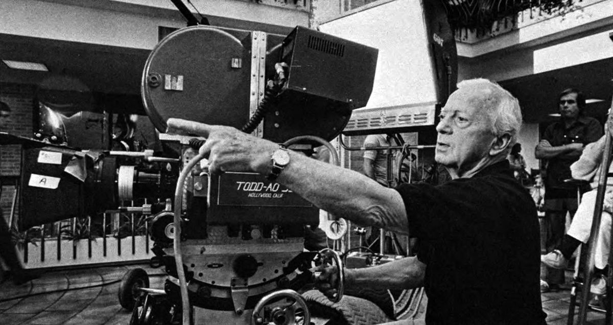 "Director of photography Ernest Laszlo, ASC checks a setup on Dallas location. On top of the Todd-AO camera can be seen the monitor of the electronic viewing system used on the production. It was helpful to the director and producer, enabling them to view ""instant dailies"" via playback on the set."