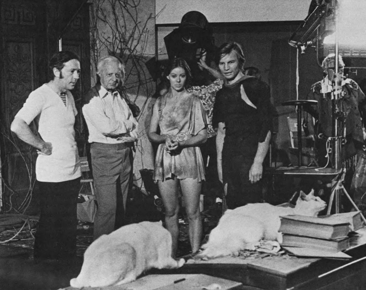 With director Michael Anderson and stars Jenny Agutter and Michael York, the cinematographer checks a couple of cats for photogenic qualities. These are two of the hundreds of cats who appear as the feline friends of Peter Ustinov in a sequence that takes place in a vine-overgrown set representing the U.S. Senate chamber 300 years in the future.