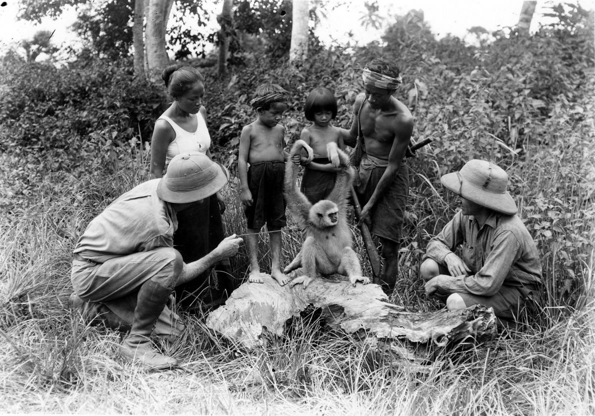 Cooper and Schoedsack, with local people in the wilds of Laos, examine a monkey while filming the docu-drama Chang: A Drama of the Wilderness (1927). Schoedsack served as cinematographer on the project.