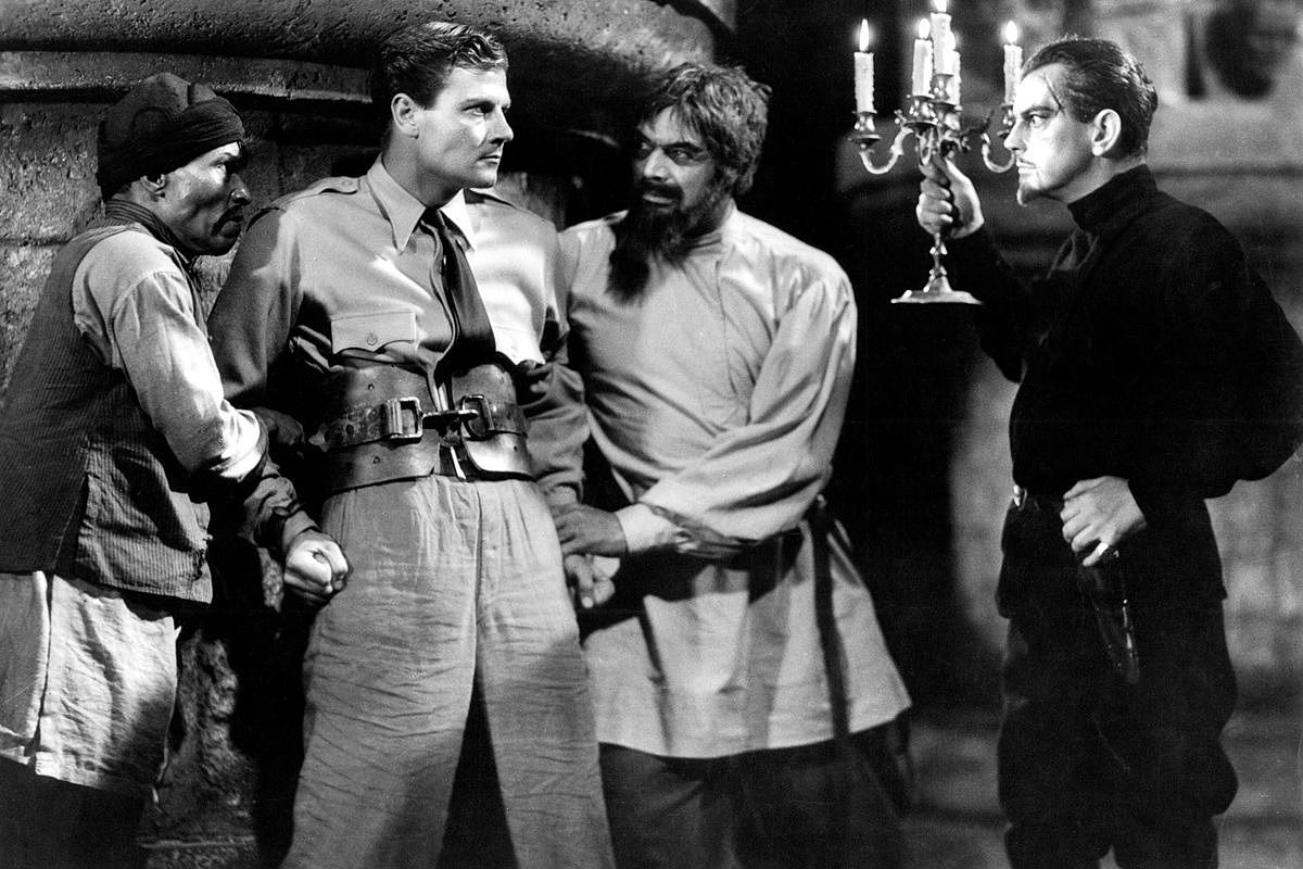 "Tartar ( Steve Clemente) and Ivan restrain Rainsford as Zaroff ""invites"" him to a nocturnal hunt."