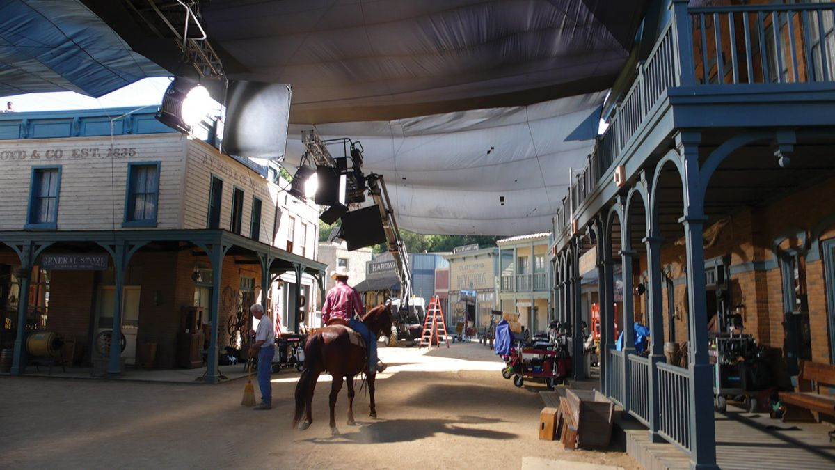 "Charcoal Grid Cloth hangs over the Universal backlot's Western Street set ""to eliminate frontlight on background action and buildings,"" Kincaid explains. ""[K 5600] 18K Alphas were cantilevered on truss mounted to condors to illuminate the interior of the saloon. Flags rigged to the truss isolated each of the HMIs to a specific window so the separate sources weren't revealed in the atmospheric smoke."""