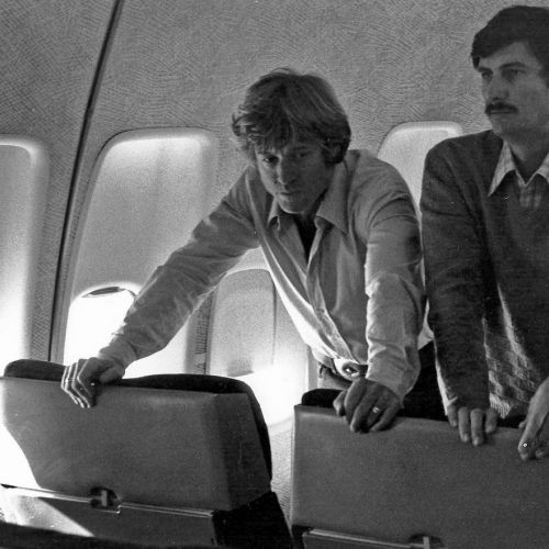 Director Robert Redford and cinematographer John Bailey prepare a scene on an airplane.