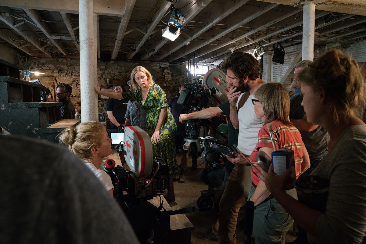 At right, Christensen (behind camera) confers with Krasinski (center) as they block out a scene with actress Emily Blunt in the farmhouse cellar.