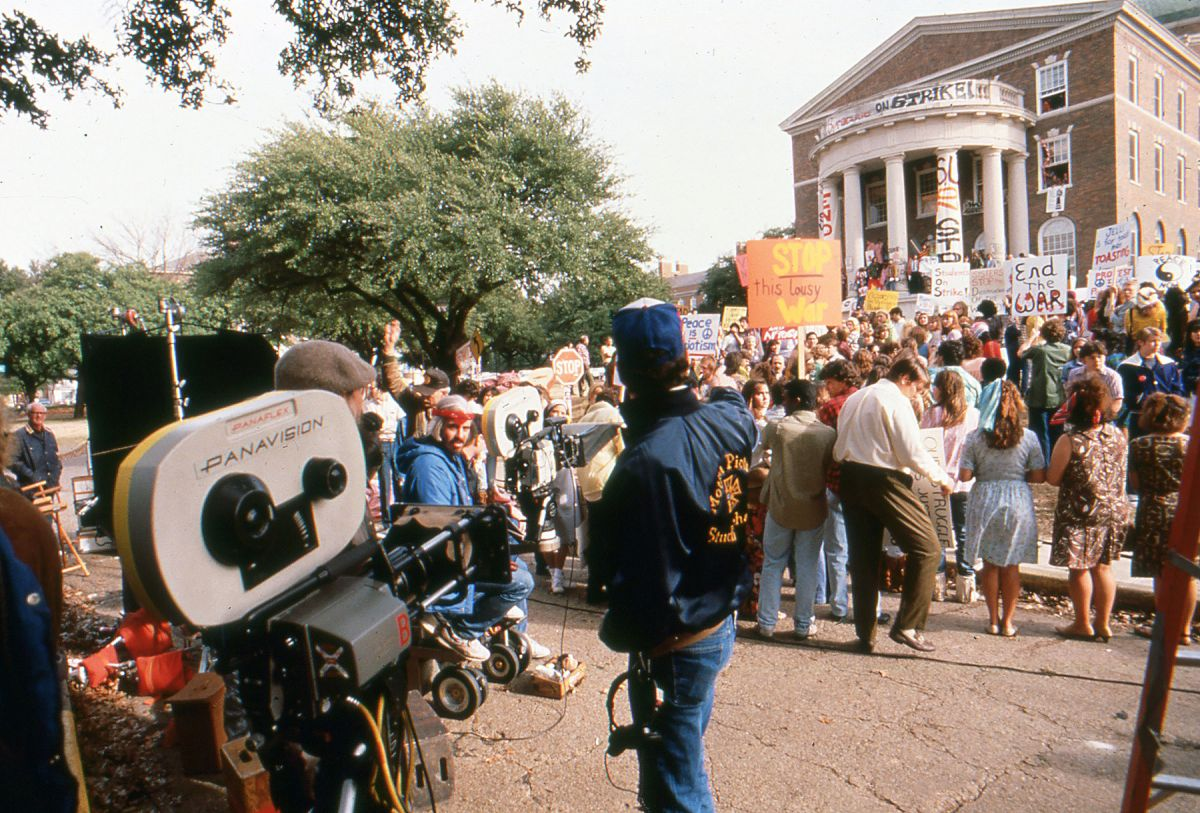 Richardson (seated, wearing red headband) prepares to roll on a crowd scene for Born on the Fourth of July (1989).