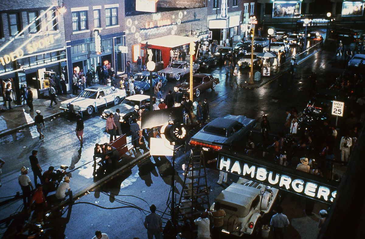 Shooting the neon-lit street scene in Tulsa, Oklahoma, the camera angles in on the cast sitting on a bench. (Photo courtesy of the Academy of Motion Picture Arts & Sciences)