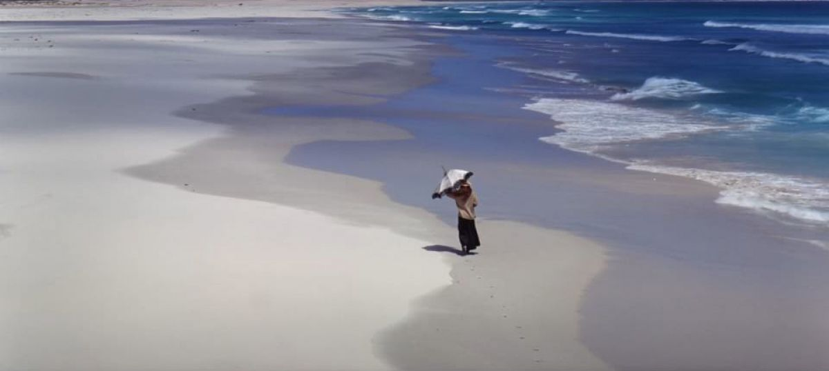 "Sarah Miles' ""Rosy"" walks along the beach."
