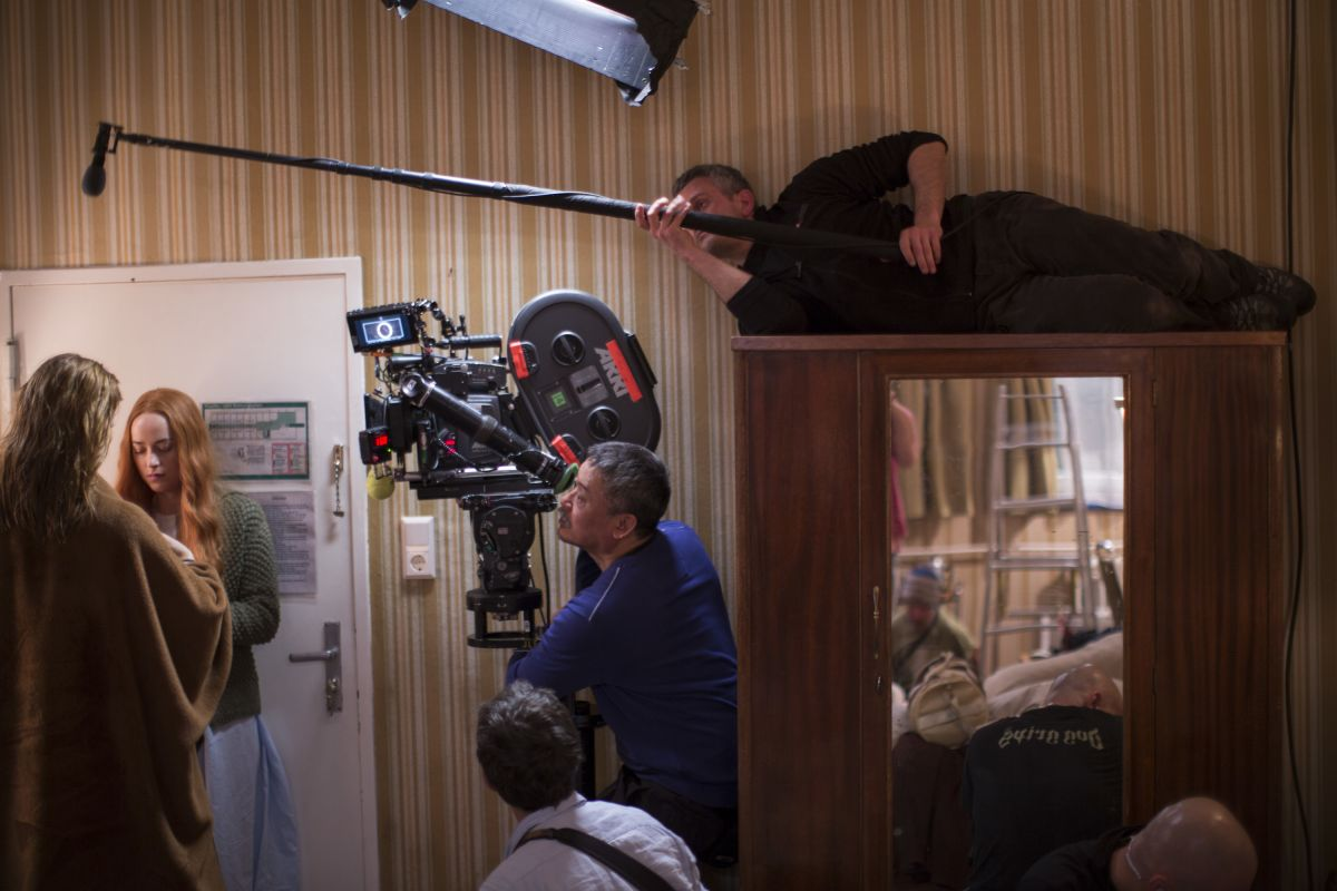 Mukdeeprom operates the camera as cast and crew work in tight quarters.