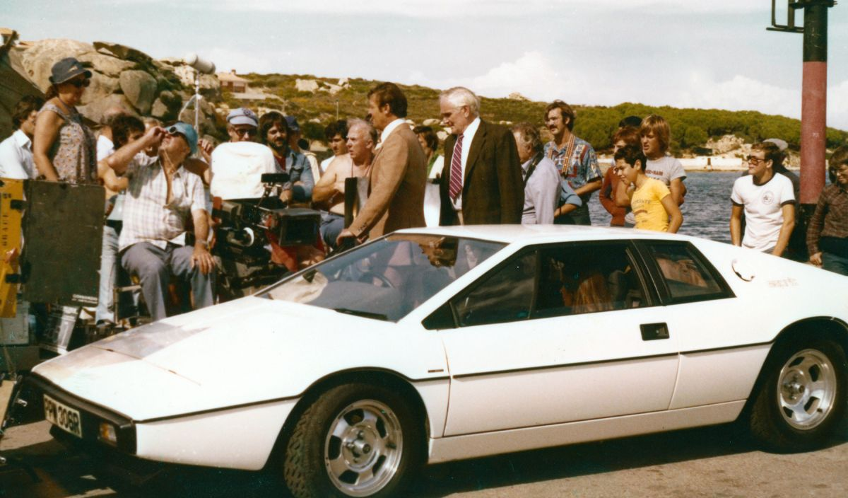 """At the camera, French director of photography Claude Renoir checks his light while shooting the scene in which gadgets master """"Q"""" (Desmond Llewelyn) hands Bond the keys to the specially equipped Lotus Esprit."""