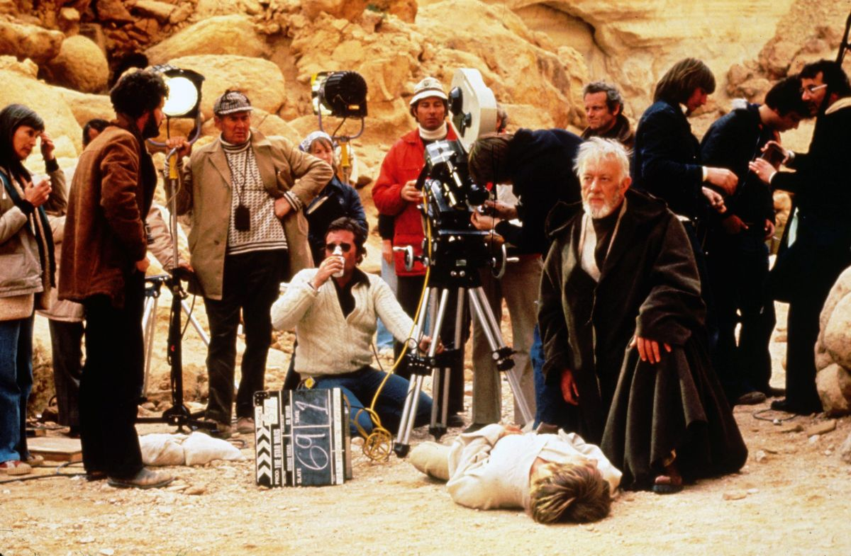 "Cinematographer Gilbert Taylor, BSC (grasping a light stand at left) observes as the Star Wars crew, and actors Alec Guinness and Mark Hamill, prepare for a take on location in Tunisia. ""The trouble with the future in most futurist movies is that it always looks new and clean and shiny,"" director George Lucas (second from left) told AC in July 1977. ""What is required for true credibility is a used future. The Apollo space capsules were instructive in that regard. By the time the astronauts returned from the moon, the capsules were littered with… candy wrappers and old Tang jars, no more exotic than the family station wagon."""