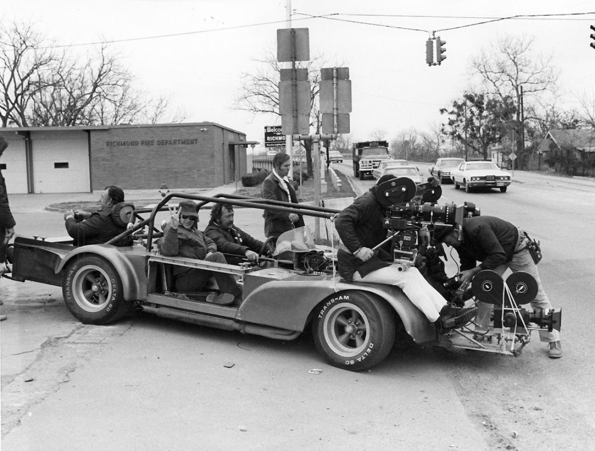 "Driver Pat Hustis, with Spielberg at his side, prepares to make a wild run in the ""Bullitt"" car, so-called because it was the vehicle originally designed to shoot the wild chase sequence in the film Bullitt. Operator Sven Walnum and Zsigmond (glimpsed between the two magazines) are strapped in behind two ""fender"" cameras in preparation for the run. A third camera has been installed for remote shooting from low camera platform on front of the vehicle."