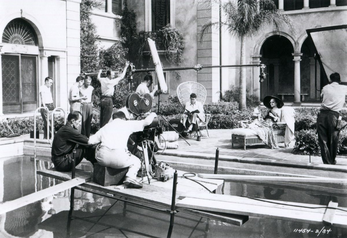 A Hollywood mansion and swimming pool was used instead of a set on the studio lot. Note reflectors employed instead of studio lamps to supply fill light on actress Gloria Swanson.