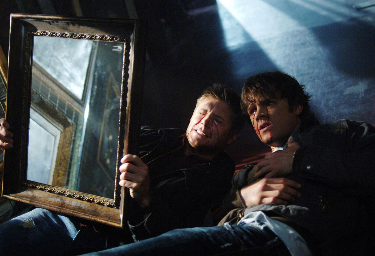 "Amidst expressionistic lighting, Sam and Dean employ a mirror to ward off evil in the Season 1 episode ""Bloody Mary."""